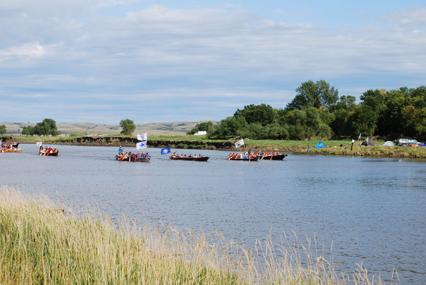 Native Americans travel to the Standing Rock camp by canoe