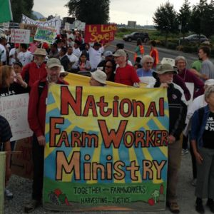 Farmworkers rally on the side of the road.