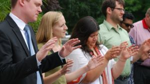 Several people pray with hands outstretched.