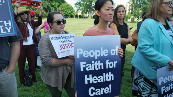 GBCS staff hold signs at health care vigil on U.S. Capitol grounds
