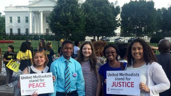 """Interns stand in front of White House holding sings that read """"United Methodist Stand For Justice,"""" and """"United Methodist Stand for Peace."""""""
