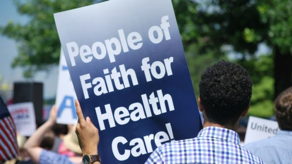 "Person holding sign which reads, ""people of faith for health care."""