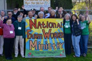 Many people stand with a sign that reads National Farm Worker Ministry: Together with Farmworkers Harvesting Justice.