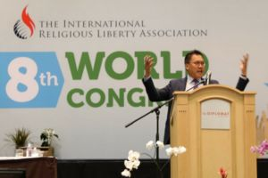 Bautista address the 8th world congress of the international religious liberty association. He stands behind a light-colored wooden podium.