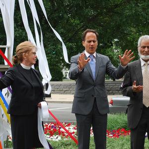 Three people lead prayer outside the United Methodist Building