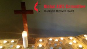 "Cross on table surrounded by tea light candles with the United Methodist Global AIDS committee Logo (the UM Cross and Flame with the words ""Global AIDS committee"")."