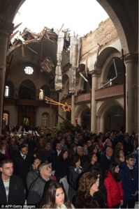 Christians worship in a church after a bombing has ruined the roof.