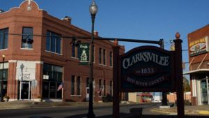 """An intersection in Clarksville, Texas with several brick buildings. There's a sign in the foreground which reads, """"Clarksville; ca. 1833; Red River County."""" The building in the background is labeled """"Chamber of Commerce."""""""