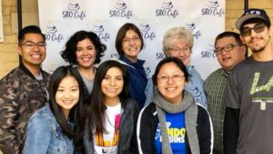 Students and Pastor Jeanne Roe Smith pose in front of a step and repeat that say 501 Cafe.