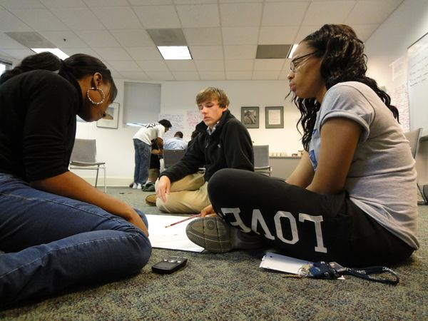 Three students sitting on the floor.