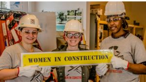 "Three women wearing safety equipment hold a yellow sign which reads ""women in construction."""