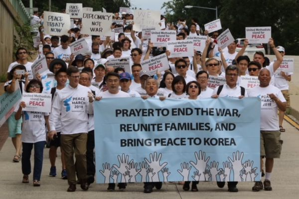 "Marchers walk on a street holding signs that read ""United Methodists stand for peace,"" and ""Peace treaty now,"" and ""Diplomacy not war."" The marchers in front of the group carry a blue banner that reads, ""Prayer to end the war, reunite families, and bring peace to Korea."""