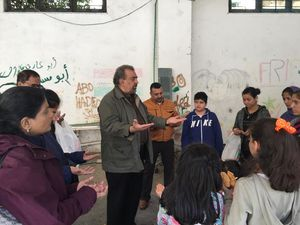 Reverend Doctor Zaki Labib Zaki leads a prayer for a group of refugees during a mission trip in Athens, Greece with the Middle Eastern United Methodist Caucus.