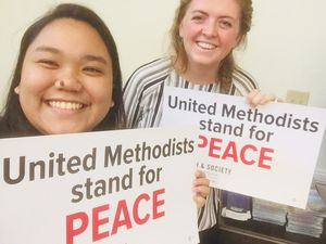 Church and Society fellows hold signs calling for peace ahead of a demonstration.