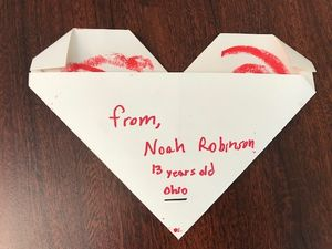 "A letter folded in the shape of a heart sits on a table. The letter reads, ""From, Noah Robinson, 13 years old. Ohio."""