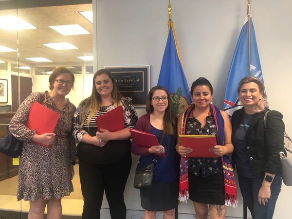 "Five people stand in front of an office door. Four of them are holding folders. Behind them are two flags and a plaque that reads, ""Senator James Lankford, Oklahoma."""