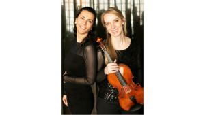 The Carr-Petrova Duo, both wearing black, pose. One has brown hair the other blond. The blond-haired woman holds a violin.