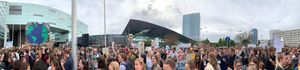 "A panoramic shot of people protesting. One sign reads, ""Save our planet."""
