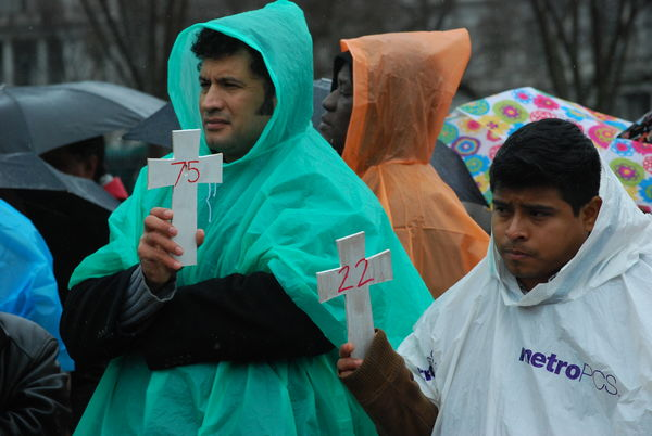 Two men hold crosses with numbers representing those killed in immigration raids