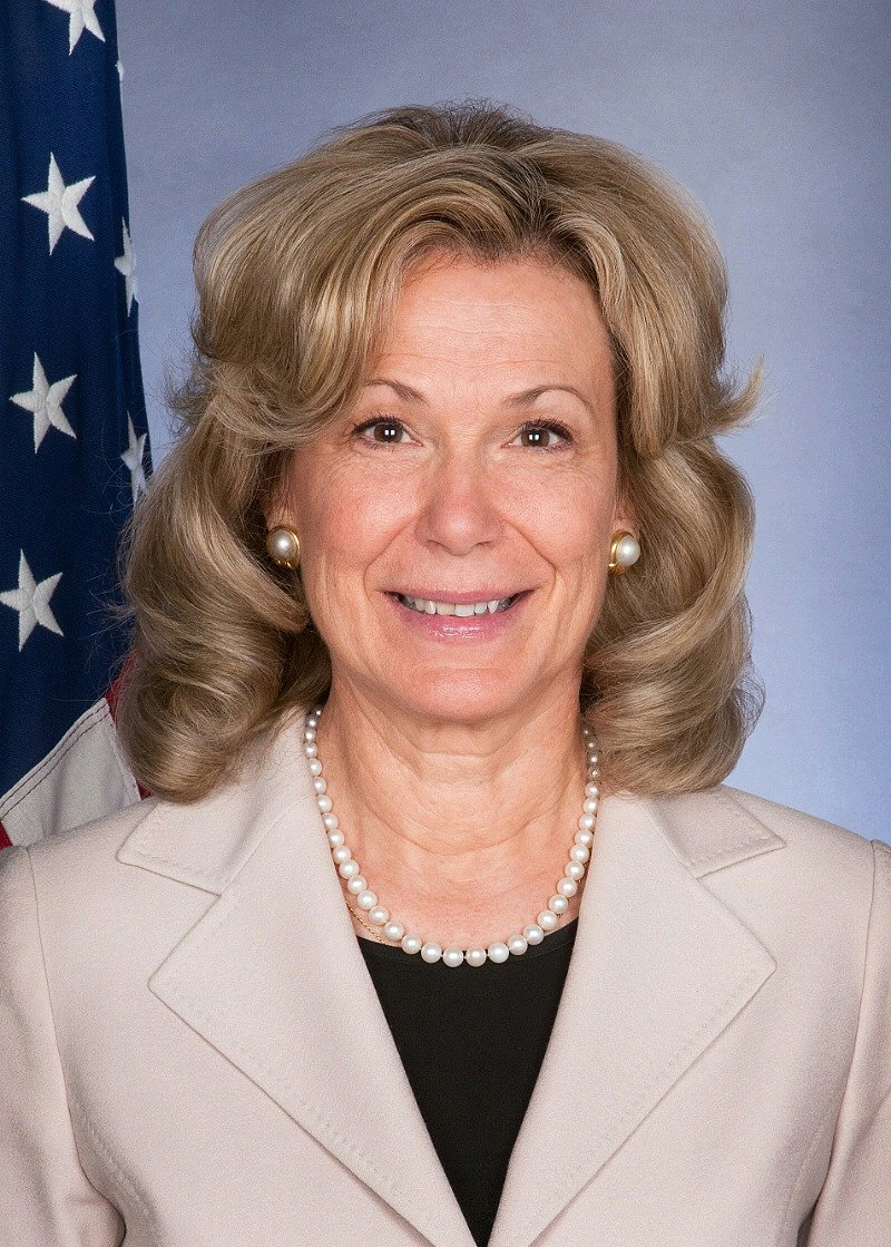 Headshot of Ambassador-at-Large Birx, a woman with blond hair. She's wear a beige jacket, black blouse and a pearl necklace. There is and American Flag in the background.