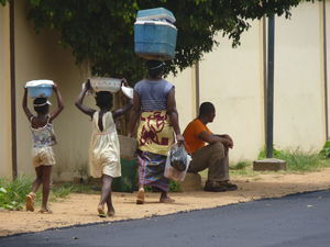 An adult and two children carry food on their heads