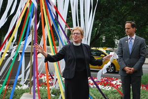 Church and Society General Secretary Leads Vigil following the Pulse Nightclub Massacre with rainbow ribbons behind her.