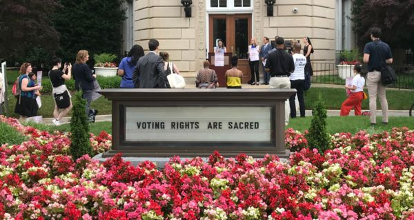 sign that says Voting is a sacred act