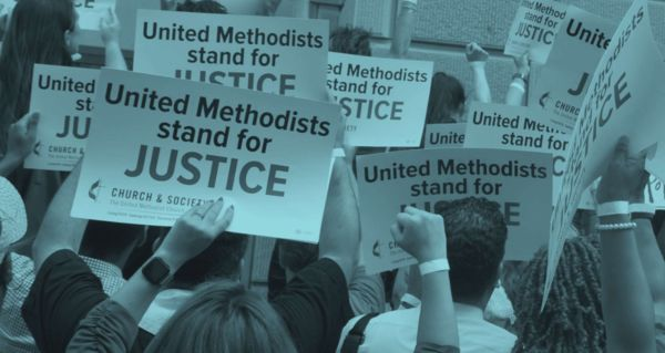 """A group of people holding signs saying """"United Methodists stand for Justice."""""""