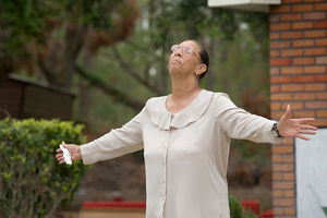 """Ella Doyle lifts her head in prayer and tells fellow parishioners to """"hold your head up"""" during an outdoor worship service at Hartzell Mt. Zion United Methodist Church in Slidell, La., shortly after Hurricane Katrina in September 2005. The church's sanctuary was ruined by the storm surge. Doyle said she rode out the storm in a boat with her husband and two sons. File Photo by Mike DuBose, UM News."""