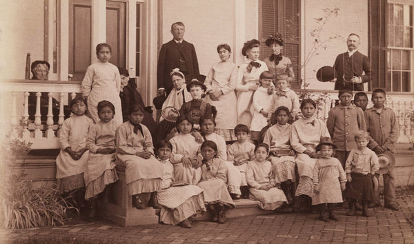 Photograph of Capt. Pratt and students at the Carlisle Industrial School, black and white photographic print, 13 cm x 21.5 cm. Capt. Richard Henry Pratt served as the head of the Carlisle Industrial School, where Native Americans were sent. Photograph circa 1900 (undated). Pratt died in 1924. Courtesy of the Yale Collection of Western Americana, Beinecke Rare Book and Manuscript Library, Yale University, New Haven, Connecticut. Public Domain via Wikimedia Commons.