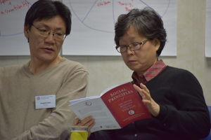 Two people read the Social Principles.