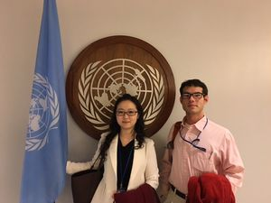 Two fellows stand in front of the U.N. flag and symbol.