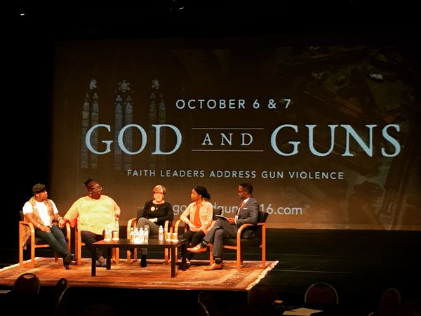 "Panel of speakers in front of backdrop that says ""God and Guns"""