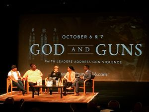 """Panel of speakers in front of backdrop that says """"God and Guns"""""""